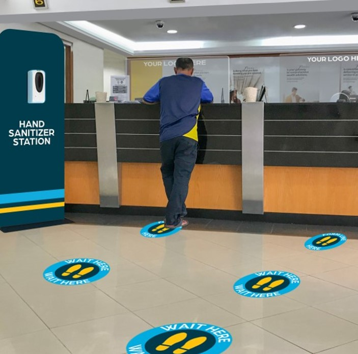 A Man Stands at a Reception Counter and There Are Floor Graphics Providing Social Distancing Cues on the Floor
