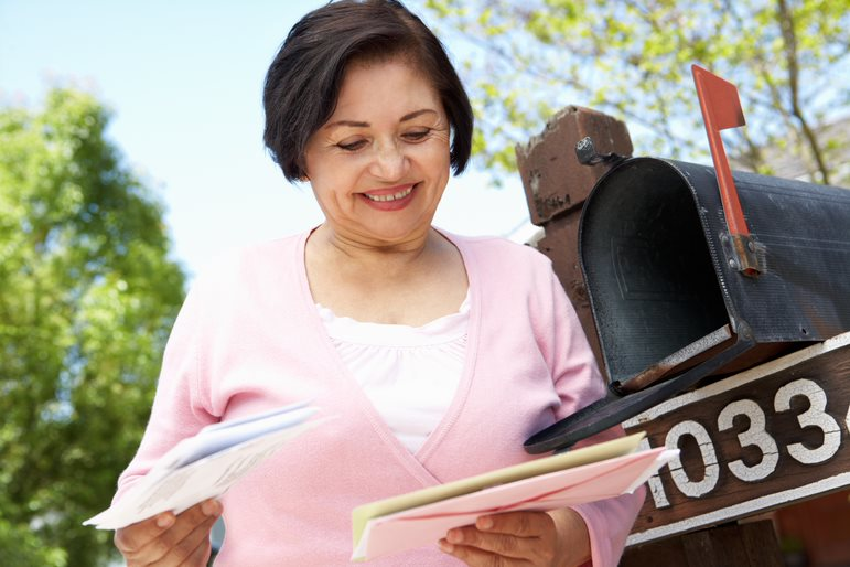 Smiling Senior Woman in a Pink Sweater Looking at Mail That She Got Out of Her Mailbox