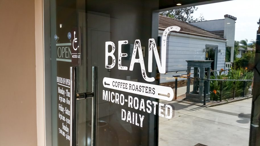 Coffee Shop Door with a Window Decal That Says Bean Coffee Roasters Micro-Roasted Daily