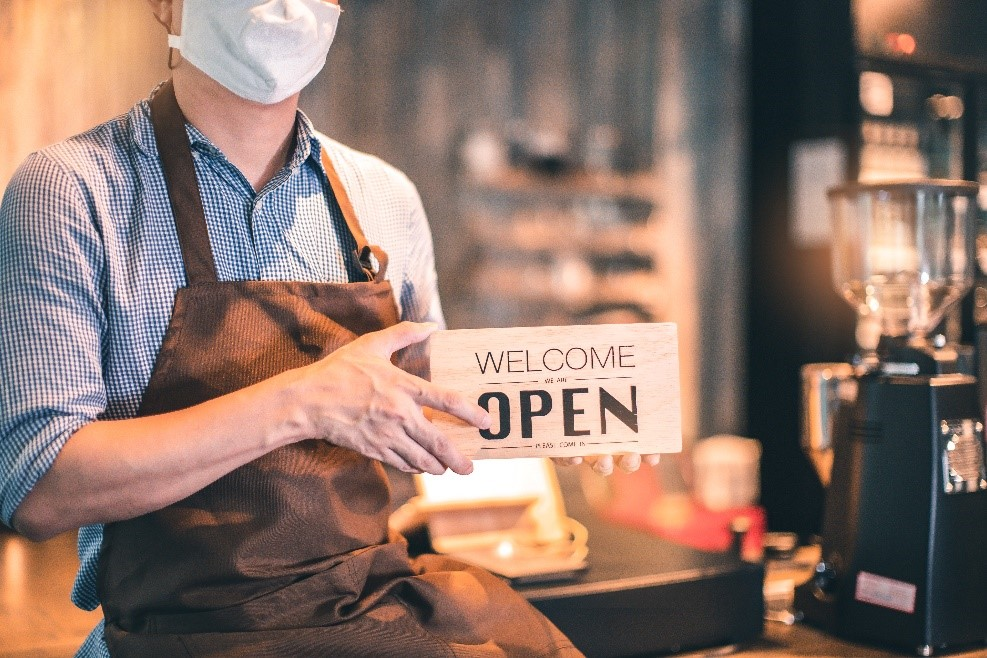 "Business owner wearing a mask and holding a sign that says ""Welcome – Open"" to greet customers."